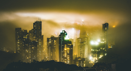 Hong Kong skyline from Victoria Peak on a foggy misty night - Wandelrust travel concept around south east asia capital cities - Warm dramatic intense filter 스톡 콘텐츠