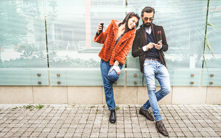 Happy hipster couple having fun with mobile smart phone at outdoors location - Friendship concept with best friends connecting and sharing content on social media - Millennial generation dating online Stock Photo