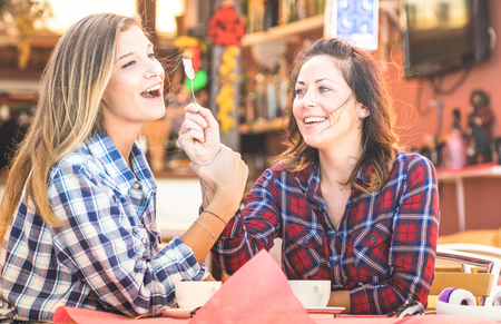 Girlfriends happy couple drinking cappuccino and laughing together - Hangout concept with young women talking and having fun at coffee bar - Warm vintage filter with focus on right girl