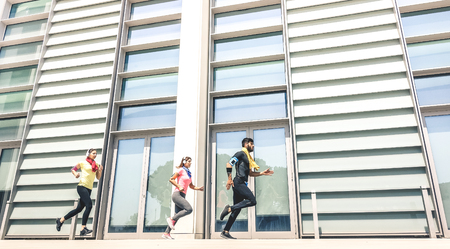 Young people running in modern urban area - Fitness girls running with male trainer coach in the city - Sport concept with friends group jogging in business center downtown on sunny day bright filter Stock Photo