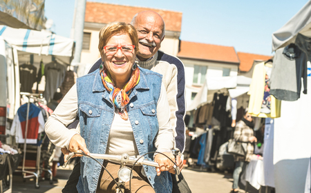 Happy senior couple having fun on bicycle at city market - Active playful elderly concept riding bike at retirement time - Everyday joy lifestyle without age limitation on warm bright sunny day filter Фото со стока