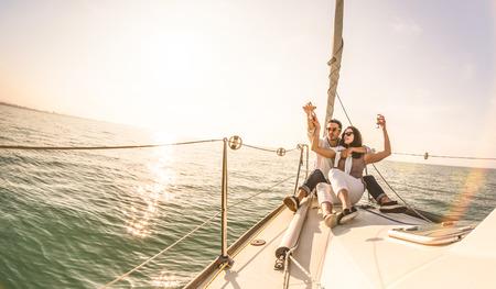 Coppia di giovani innamorati in barca a vela con champagne al tramonto - Esclusivo concetto di lusso con uno stile di vita ricco di persone millenarie in tournée in tutto il mondo - La retroilluminazione morbida si concentra sul caldo filtro solare