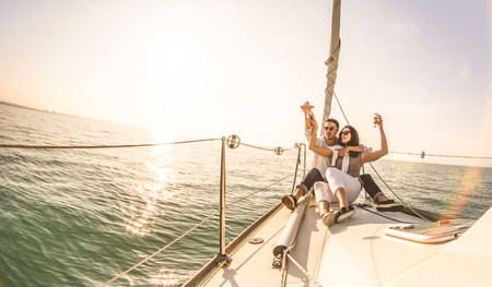 Young lovers couple on sail boat with champagne at sunset - Exclusive luxury concept with rich millennial people lifestyle on tour around the world - Soft backlight focus on warm sunshine filter 免版税图像