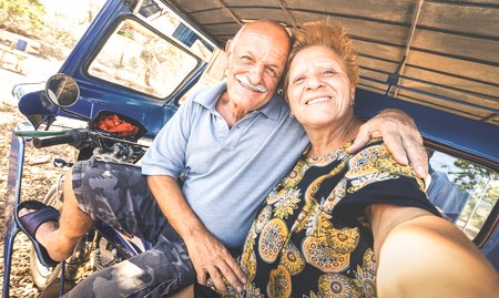 Happy senior couple taking selfie on tricycle in Philippines travel - Concept of active playful elderly during retirement - Everyday joy lifestyle without age limitation - Warm afternoon filter tones Фото со стока