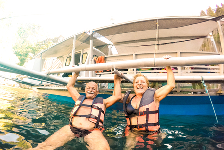 Senior couple vacationer having genuine playful fun at beach in Philippines - Snorkel boat trip in exotic scenario - Active elderly and travel concept on tour around world - Bright sunny filter Stok Fotoğraf