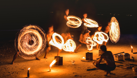 Group of firestarter performing amazing fire show with sparkles at night - Full moon party event festival in Thailand nightlife at beach resort - Wanderlust and travel concept around the world Stock Photo
