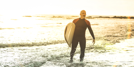 Guy surfer walking with surfboard at sunset in Tenerife - Surf long board training practitioner in action - Sport travel concept with soft focus due to backlight - Warm sunshine color filtered tones Stock Photo