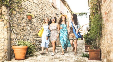 Multiracial millennial girlfriends walking in old town tour - Happy girl best friends having fun around city streets - University women students on travel vacations - Bright edsaturated vintage filter