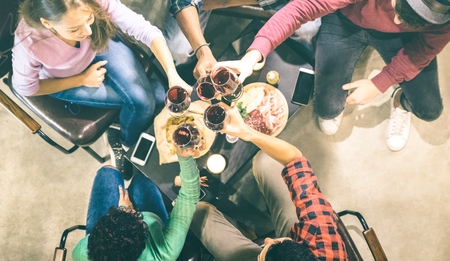 Overhead view of millennial friends tasting red wine and having fun at fashion winery - Multiracial friendship concept with people enjoying time out drinking together - Desaturated neon filter