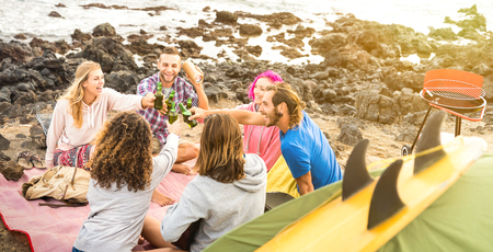 Friends backpackers having fun together at beach camping party - Happy friendship travel concept with young people travelers playing guitar and drinking beer at summer surf camp - Warm vivid filter Stock Photo