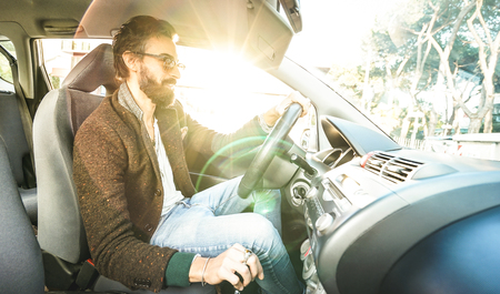 Young hipster fashion model driving car - Happy confident man with beard and alternative mustache smiling at business roadtrip - Lens flare halo as part of composition - Bright vintage filter