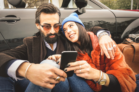Hipster couple having fun with mobile smart phone at car roadtrip - Friendship concept with best friends connecting and sharing content on social media - Millennial generation as fashion influencer Stock Photo