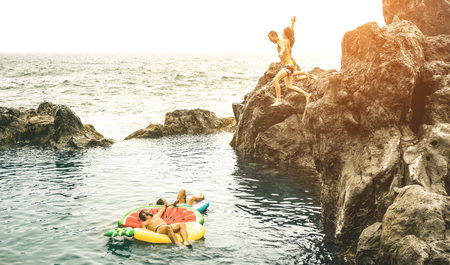 Young friends vacationers jumping on natural pool at travel beach location - Sporty people having fun diving in to the sea - Wanderlust lifestyle concept on warm vintage filter with sunshine halo Stock Photo