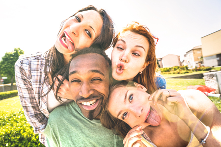 Happy multiracial friends group taking selfie sticking tongue out with funny faces - Young people sharing stories on social network community - Millennials lifestyle concept on vivid vintage filter