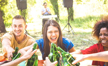 Multiracial millenial friend having fun at barbecue garden party with music - Friendship concept with young happy people toasting beer bottle at summer hangout - Guys and girls on warm sunshine filter Stock Photo