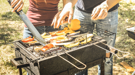 Couple of friends cooking vegetables on barbecue - Aubergines and peppers cooked on grill at bbq garden party - Pic nic concept with lunch outdoors on spring summer time - Bright vivid vintage filter