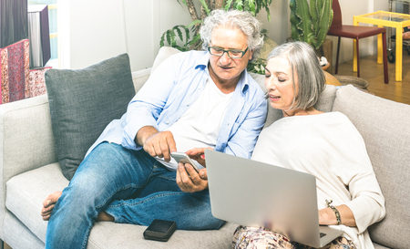 Senior retired couple using laptop computer at home on sofa - Elderly and technology concept with mature people at online shopping - Modern situation of internet connection booking - Neutral filter Stock Photo