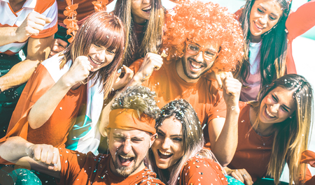 Young football supporter fans cheering with flag and confetti watching soccer cup match at stadium - Friends people group with red t-shirts having excited fun on sport world championship concept Stock Photo