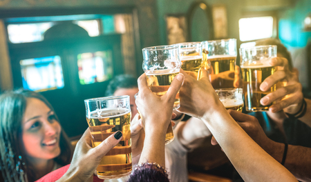 Friends group drinking and toasting beer at brewery bar restaurant - Friendship concept with young millenial people having fun together on happy hour at vintage brew pub - Focus on middle pint glass Stock Photo