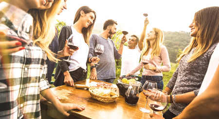 Millenial friends having fun time drinking red wine oudoors - Happy fancy people enjoying harvest at farmhouse vineyard winery - Youth friendship concept together at pic nic garden party - Warm filter Stockfoto
