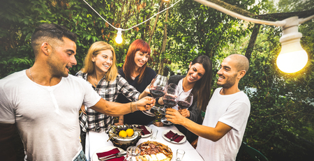 Happy friends having fun drinking red wine at backyard garden party - Youth friendship concept together at farm house vineyard winery - Focus on background young women with bulb lights lighting on men