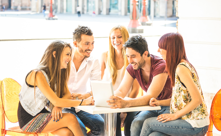 Friend group sitting at restaurant bar having fun with tablet pc - Connected community of young students people using portable computer - Millennial generation concept sharing content on social media