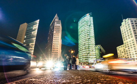 BERLIN, GERMANY - 14 OCTOBER 2016: Potsdamer Platz with tourists and traffic jam at blue hour - Low point of view composition with blurred car lights tracks - German capital by night