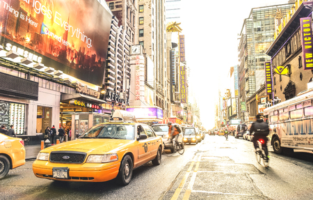NEW YORK - MARCH 27, 2015: yellow taxi cab and everyday life near Times Square in Manhattan downtown before sunset - Intersection of 7th Avenue with 42nd Street - Warm sunshine filtered color tones 에디토리얼