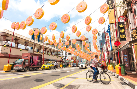 SINGAPORE - FEBRUARY 12, 2015: man with bike on South Bridge Road near the corner with Temple Street in Chinatown district with colorful decorations for the upcoming Chinese New Year