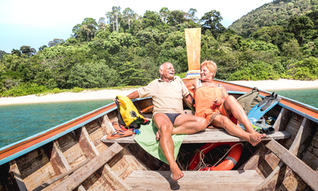 Senior couple vacationer relaxing at island hopping tour after beach exploration during snorkel boat trip in Thailand - Active elderly and travel concept on tour around world - Warm day bright filter Stock Photo
