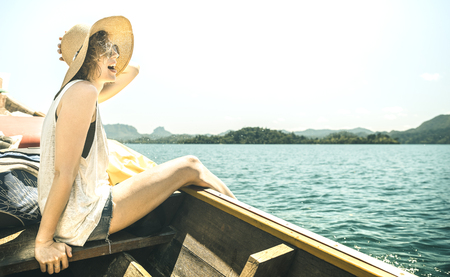 Young woman solo traveler at boat trip excursion at lake - Wanderlust travel concept with adventure girl tourist wanderer on Thailand and South East Asia adventure - Warm azure filter