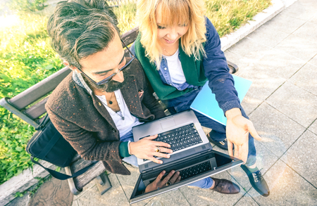Young hipster couple using computer laptop in urban outdoor location - Modern fun concept with millenials on new trends and technology - Wireless connection and web internet social media networking