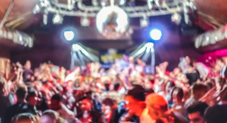 Blurred people dancing at music concert event - Abstract defocused background of disco club after party at live stage festival - Nightlife entertainment concept - Bright spotlight filter Stock Photo