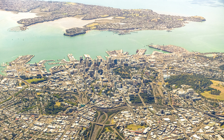 Aerial view of Auckland skyline with modern buildings and green areas - New Zealand modern city with spectacular panorama - Soft azure and greenish filter
