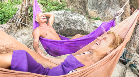 Senior retired couple vacationer relaxing on hammock at beach - Active youthful elderly and happy travel concept on tour around world exploring Thailand nature beauties - Bright living coral filter