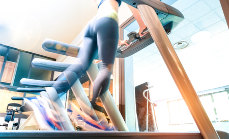 Low section view of active sportswoman running on treadmill at gym fitness studio - Healthy lifestyle concept with woman exercising at running machine wearing leggings sport clothes - Blurred motion