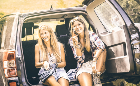 Young female best friends using mobile smart phone and having fun with at car roadtrip moment - Wanderlust concept with women girlfriends at happy travel vacation on the road - Warm vintage filter
