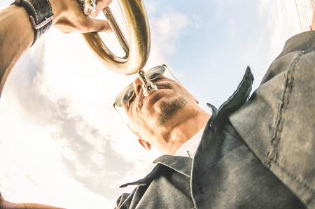 Artist performing trumpet solo jazz against sky - Music and street art concept at open air club location with groove mood atmosphere - Warm afternoon color tones with lower point of view composition