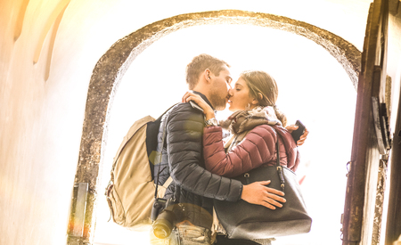 Travel couple in love kissing outdoors at city tour excursion - Young happy tourists enjoying romantic moment at sunset - Relationship concept with lovers at first date - Warm sunshine filter