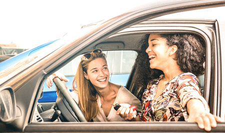 Young female best friends having fun at car roadtrip moment - Transportation concept and urban ordinary life with women girlfriends at happy travel vacation on the road - Bright azure filter Stock Photo