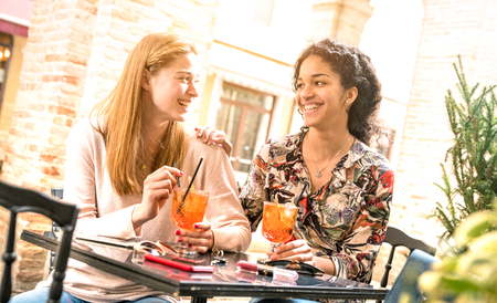 Young women drinking cocktails at bar restaurant outside on happy hour time - Friendship concept with millenial girlfriends having genuine fun together - Happy girls best friends on warm bright filter