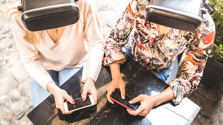 Girl friends playing on vr glasses outdoor - Virtual reality and wearable tech concept with young people having fun together with headset goggles - Generation z digital trends - Bright contrast filter