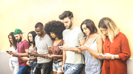 Multiracial friends using mobile smartphone at university coampus - Millenial people addicted by smart phones - Tech concept with always connected millennials on social networks - Bright warm filter