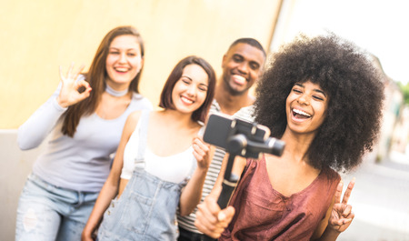 Millennial people taking video selfie with stabilized mobile phone  - Young friends having fun on new tech trends - Youth and friendship concept with millenials sharing moments on social media network