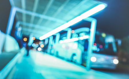 Blurred defocused background of bus station terminal at night - Abstract concept of transportation with blurry backdrop and copy space - Vivid azure filter and tilted composition Stock Photo