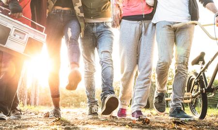 Freunde, die im Stadtpark mit Hintergrundbeleuchtung und Sunflare Halo spazieren gehen - Milleniales Freundschaftskonzept und gemischtrassige junge Leute auf alternativer Mode, die zusammen Spaß haben - Beinansicht mit weicher Bewegungsunschärfe