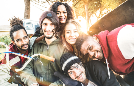 Multiracial best friends taking selfie at bmx skate park contest - Happy youth and friendship concept with young millenial people having fun together in urban city area - Bright warm sunshine filter Stock Photo