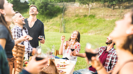 Young friends having fun drinking red wine on barbecue pic nic at garden party - Happy people eating tasty meal at country side fancy restaurant - Food and beverage concept on warm afternoon filter