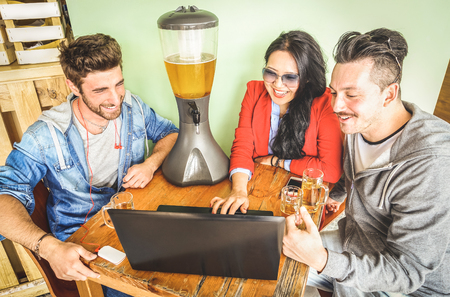 Friends using computer laptop at brewery bar - Connected community of young students people having fun with pc device and beer - Millennial generation concept sharing content on social media network Stock Photo