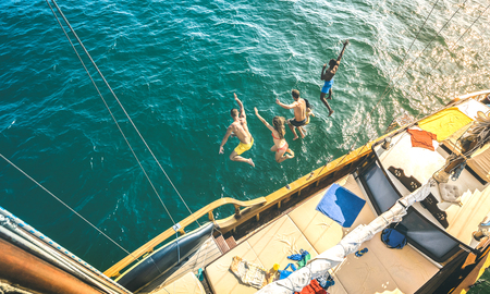 Aerial view of happy millenial friends jumping from sailboat on sea ocean trip - Rich guys and girls having fun together in exclusive boat party day - Luxury vacation concept on contrast bright filter
